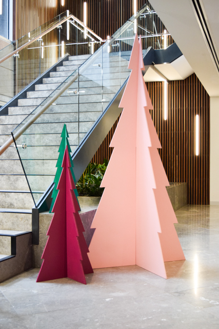 Three plywood Christmas tree next to stairs
