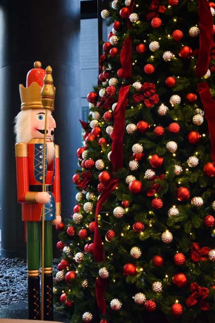 Nutcracker standing next to Christmas tree