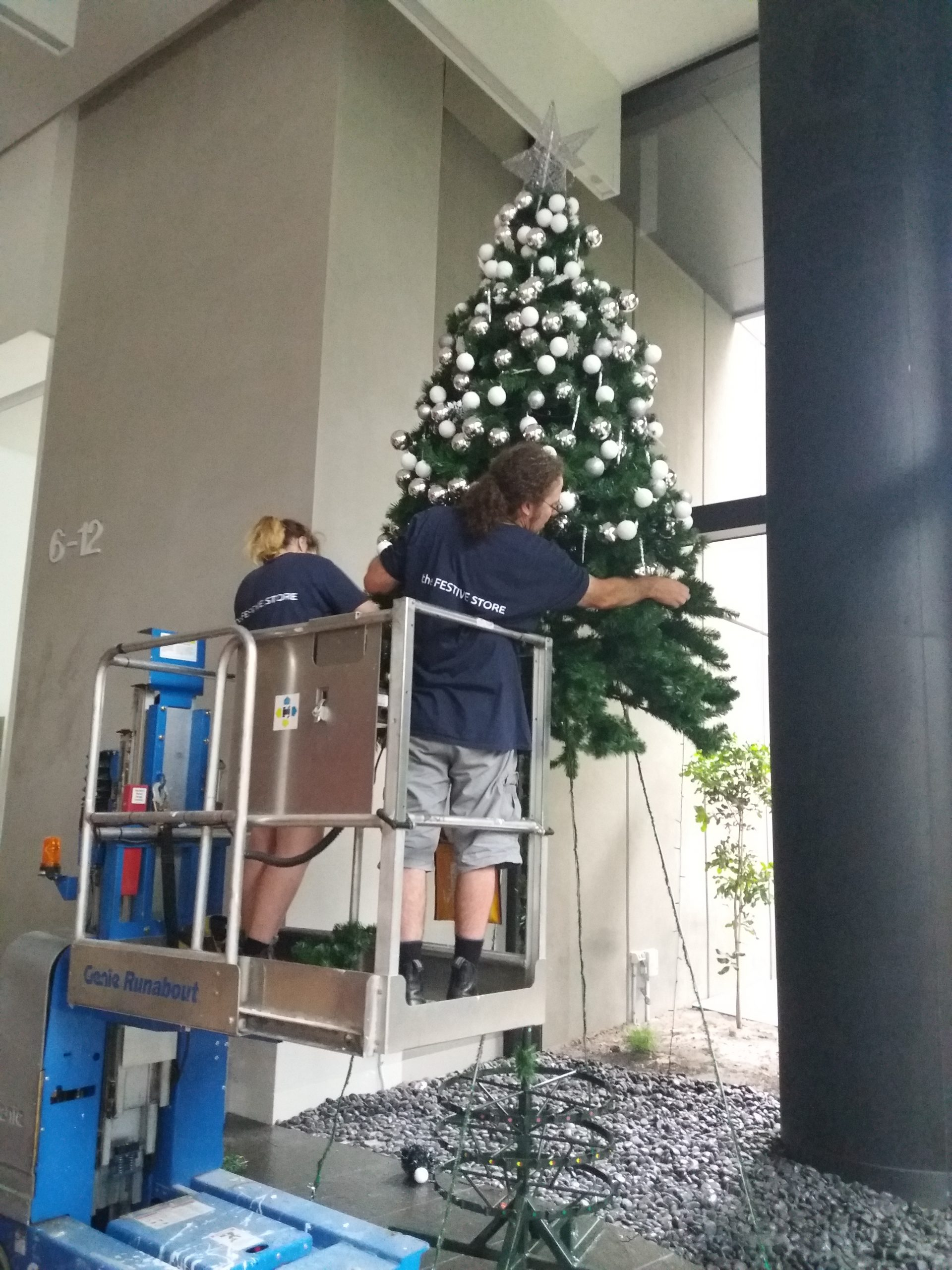 Christmas tree being installed with a scissor lift