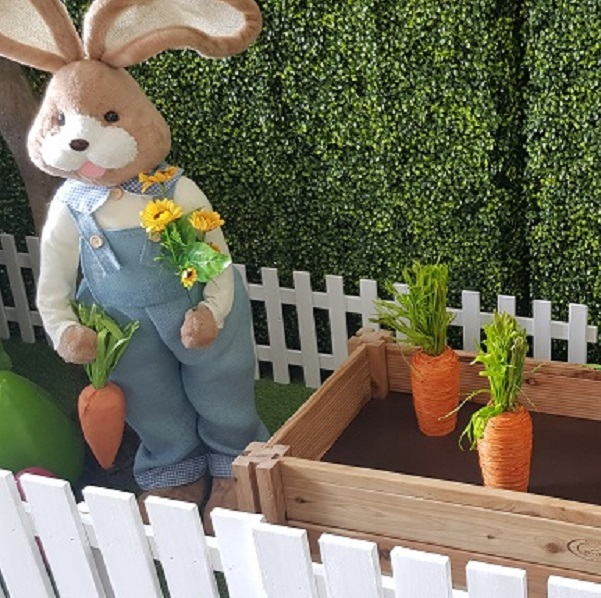 Display featuring an upright tan easter bunny wearing a white top with blue overalls. The bunny is holding a fake carrot in hone hand and a bunch of yellow flowers in the other hand. Next to the bunny is a pretend garden bed with two orange carrots. The scene is currounded by a short white picket fence in front of a green artificial folliage hedge