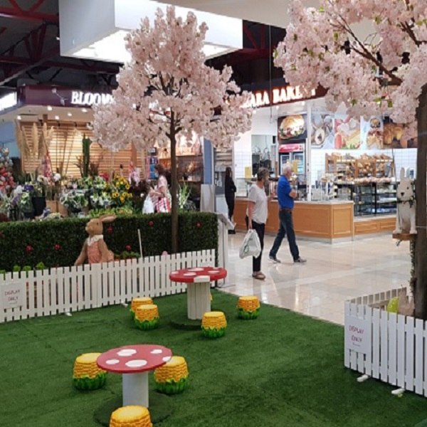 An Easter Display inside a shopping centre featuing a garden with mushroom seating, pale pink cherry blossom trees and easter rabbits