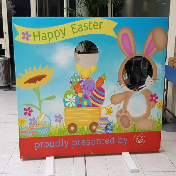 A large Easter Photoboard sign with an easter bunny and chicken with the heads missing allowing customers to place their faces into the scene. There is a large subflower and a small wheeled wagon carrying painted eggs and carrots