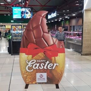 A large flat sign in the shape of an easter egg with a bite taken out of the top edge. Happy Easter is written on the gold foil covering the bottom half of the egg which also has a large red bow around it