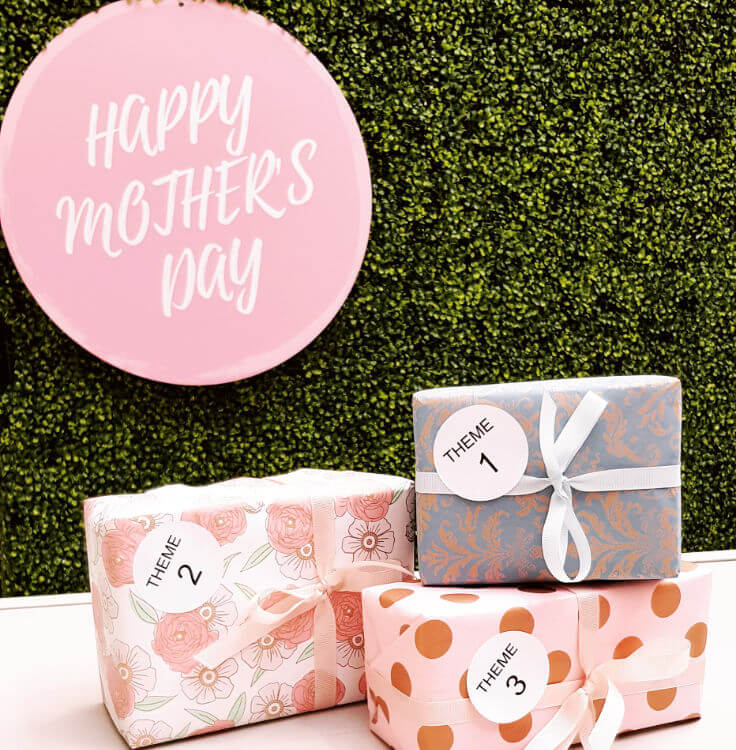 Three rectangular presents in three diffrent patterns beneath a pink sign with happy mothers day in white text